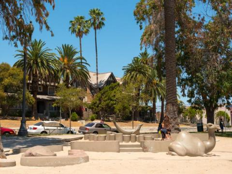 From left to right, a concrete turtle, seal, and camel in the sand for people to sit on. Two kids play on the right.