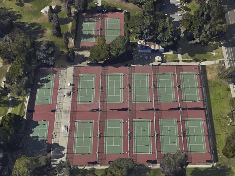 A birds eye view of tennis courts from above. Most are in a six by two area, but there are two courts on their own in the top left